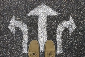 image looking down at shoes standing on chalk drawings of arrows pointing in different directions